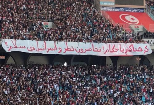 الجمهور التونسي يرفع لافتة: كرهناكم يا حكام..  تحاصرون قطر وإسرائيل في سلام!